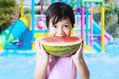 Kid eats watermelon at pool Royalty Free Stock Photography