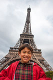 Kid at the Eiffel Tower. A happy kid at the Eiffel Tower on a cloudy day.  Bright red rain coat, tan face, big smile Royalty Free Stock Images