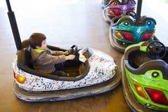 Kid in electric bumper car. Amusement park royalty free stock photo