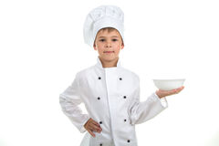 A kid with an empty plate on his hand wearing chef uniform, isolated on white background. Stock Photos