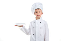 A kid with an empty plate wearing chef uniform on white background. Royalty Free Stock Images