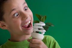 Kid with energy saving bulb Stock Image