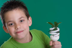 Kid with energy saving bulb Royalty Free Stock Photography