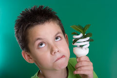 Kid with energy saving bulb Royalty Free Stock Photos
