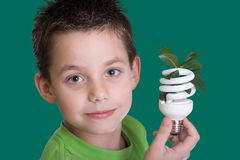 Kid with energy saving bulb Royalty Free Stock Images