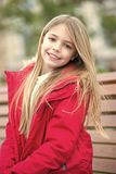 Kid enjoy autumn day. Child with blond long hair smile outdoor. Leisure, relaxation, lifestyle. Girl in red coat sit on bench in park. Happy childhood concept royalty free stock images