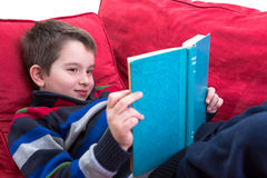 Enjoy Reading. Kid enjoy reading the novel on the comfortable red couch Stock Image