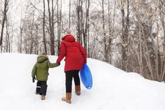Kid enjoy riding on ice slide in winter. Little boy with his mother climb the hill stock image