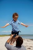 Kid Enjoying as His Dad Lifts Him Stock Images
