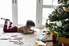 Kid enjoying the coloring book in christmas decorated room Royalty Free Stock Photos