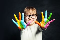 Kid enjoying his painting. Cute child girl with colorful hands on classroom blackboard background. Arts and creative education. Concept stock image