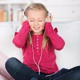 Kid enjoying music with closed eyes. Portrait of a female kid enjoying music with closed eyes Stock Image