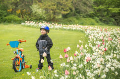Kid enjoying outdoors scenery. Child with his first bike enjoys outdoors scenery in the park Stock Image