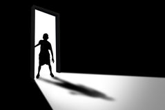 Kid Enters Dark Room Concept of Unknown and Fear. Silhouette of boy entering dark room with bright light in doorway Royalty Free Stock Photo
