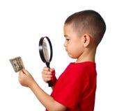 Kid examining money royalty free stock image
