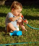Kid exploring water hose. Little kid exploring water hose royalty free stock images
