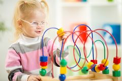 Kid in eyeglases playing colorful toy in home Stock Image