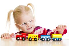 Kid in eyeglases playing toy train isolated. On white Royalty Free Stock Photos