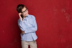 Smart boy in eyeglasses talking by mobile phone. royalty free stock image