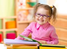 Kid in eyeglasses or spectacles reading books in her room royalty free stock photo