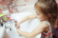 Kid wearing t-shirt washing hands in bathroom with soap. Kid with fair hair, wearing t-shirt and thoroughly washing hands in bathroom with water and soap Royalty Free Stock Images