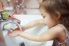 Kid wearing t-shirt washing hands in bathroom with soap. Kid with fair hair, wearing t-shirt and thoroughly washing hands in bathroom with water and soap Stock Images