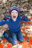 Kid at fall. Little kid enjoying autumn time at the park Royalty Free Stock Photography