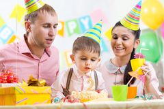 Kid with family blowing candle on birthday cake Stock Image