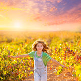 Kid farmer girl running in vineyard field in autumn. Red leaves royalty free stock images