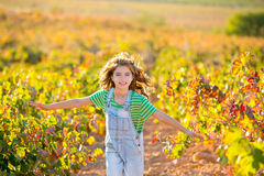 Kid farmer  girl running in vineyard field in autumn Royalty Free Stock Photos
