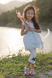 Kid fashion. Cute little asian girl wearing white clothes and flower grass in her hand. stock image