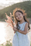 Kid fashion. Cute little asian girl wearing white clothes and flower grass in her hand. Stock Photos