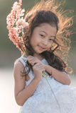 Kid fashion. Cute little asian girl wearing white clothes and flower grass in her hand. royalty free stock photo