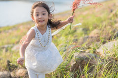 Kid fashion. Cute little asian girl wearing white clothes and flower grass in her hand. Royalty Free Stock Images