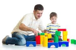 Kid and father play with building blocks Stock Photography