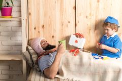 Kid and father playing hospital. Patient with flu lying in bed under woolen blanket. Doctor visiting sick bearded man at. Kid and father playing hospital stock images