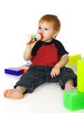 Kid with a feeding bottle and cubes Royalty Free Stock Photography