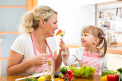 Kid feeding mother vegetables in kitchen Stock Images