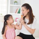 Kid feeding mum ice cream Stock Photos