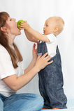 Kid feeds her mother an apple. Royalty Free Stock Photography