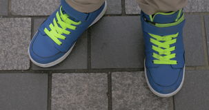 Kid feet in blue trainers on paved sidewalk stock video footage