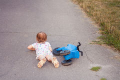 Kid fell down of her bike. Active small girl playing and cycling outdoors fell down of her bike Royalty Free Stock Photography