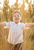 Kid in field playing with spikes at summer sunset Stock Images