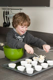 Kid Filling Cakecups With Dough Stock Images