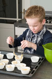 Kid Filling Cakecups With Dough Stock Photo