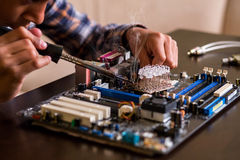 Kid fixes motherboard on table. Stock Photos