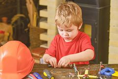 Kid fixing two metal details. Concentrated boy working with bolts. Preschooler helping in workshop.  stock images