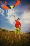 Kid flies a kite into the blue sky. Happy Little boy flies a kite into the blue sky Royalty Free Stock Photo