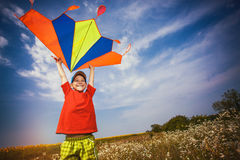 Kid flies a kite into the blue sky. Happy Little boy flies a kite into the blue sky Royalty Free Stock Photography