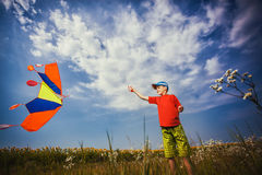Kid flies a kite into the blue sky Royalty Free Stock Photography